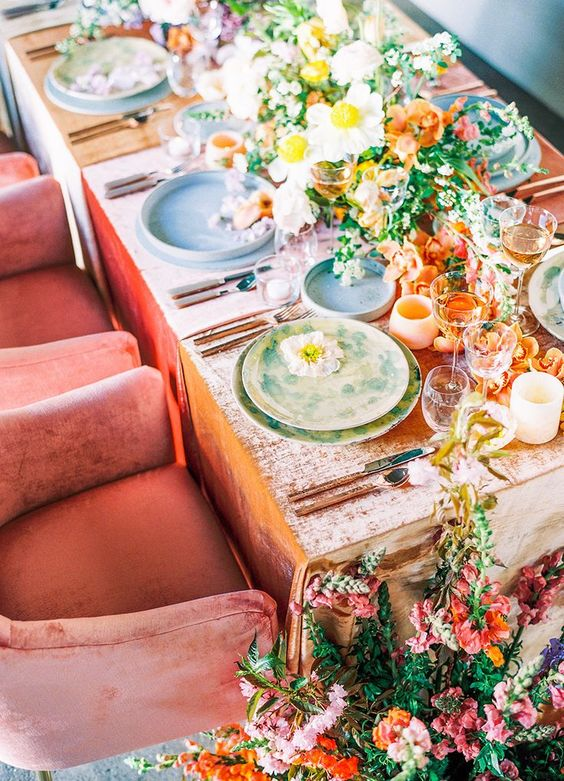 a bright wedding table setting with yellow, orange and white blooms, a peachy tablecloth and colorful plates, peachy candleholders and pink and orange blooms on the floor