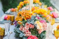 a bright wedding table with yellow, blush and white blooms and pale greenery, amber glasses and tall candles is amazing