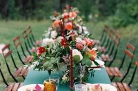 a bright wedding tablescape with a green tablecloth and pink napkins, red and orange blooms and greenery, amber glasses