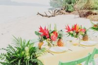 a bright wedding tablescape with a sunny yellow tablecloth, bold red blooms and greenery, tropical leaves and pineapples