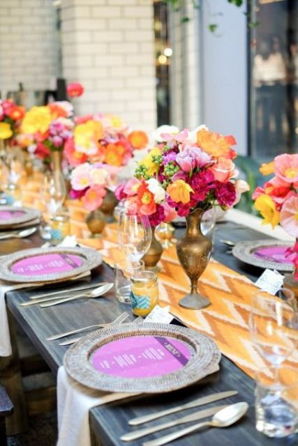 a bright wedding tablescape with an orange chevron table runner, hot pink menus, yellow, hot pink, orange and fuchsia blooms