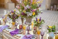 a cheerful summer wedding tablescape with lilac and purple napkins, lilac and amber glasses, yellow, lilac and purple blooms and greenery