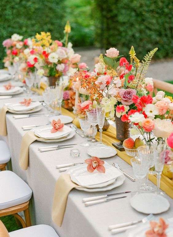 a cheerful wedding tablescape with dusty pink, red, yellow blooms and greenery, pale yellow napkins and a mustard runner