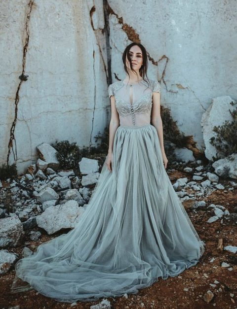 a chic and beautiful grey wedding dress with a sheer bodice with lace appliques and a tulle skirt with a train