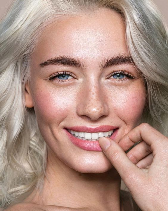 a chic nude makeup with brushed eyebrows, a bit of mascara, a pink lip, a touch of rouge and a great tone with highlights