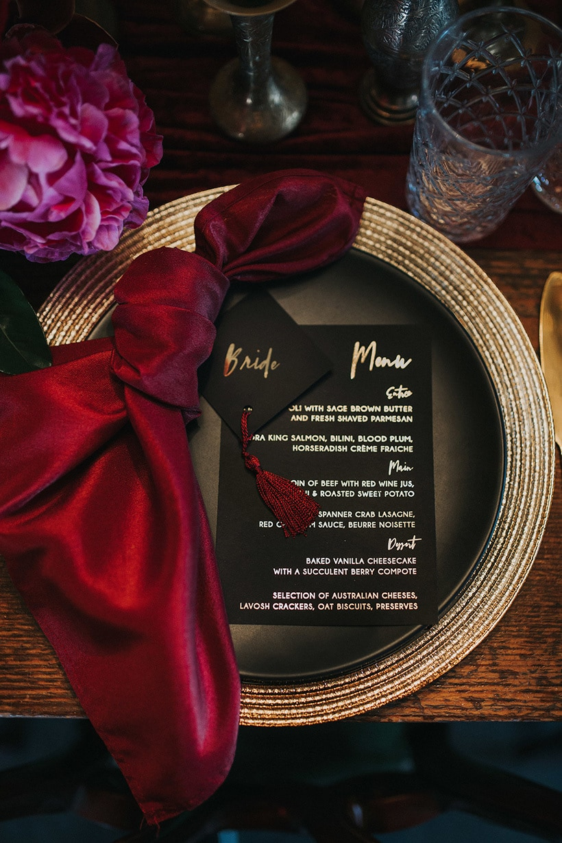 a chic place setting with a metallic charger, black plates and menus plus a deep red napkin