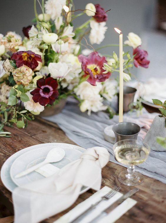 a chic tablescape with a grey table runner, bold burgundy and neutral blooms and tall candles