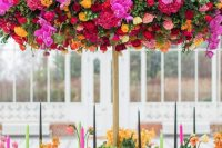 a colorful and luxurious wedding tablescape with fuchsia, hot pink, yellow and red blooms, greenery, colorful candles and an oversized floral installation over the table