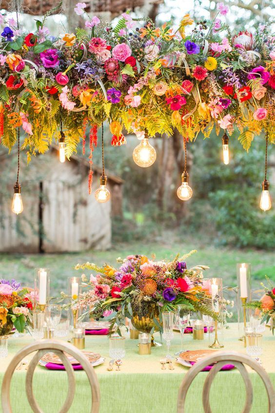a colorful boho wedding tablescape with a green tablecloth, hot pink, purple and orange blooms and fern leaves, candles and gold touches