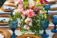 a colorful summer wedding tablescape with blue glasses, woven chargers, pink, hot pink and yellow blooms and greenery