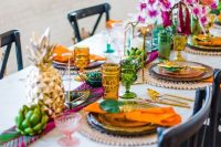 a colorful tropical boho wedding tablescape with colorful glasses, gold pineapples, gold candle lanterns and super bright blooms