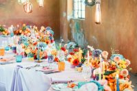 a colorful wedding table setting with blue, red, yellow and orange blooms, colorful candles, glasses and candleholders plus hanging bulbs