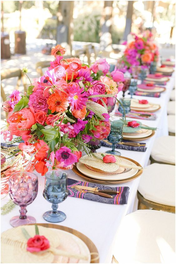 a colorful wedding table setting with hot pink and red blooms, purple and blue glasses, navy and pink napkins and greenery
