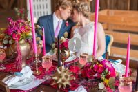 a colorful wedding tablescape with hot pink blooms, hot pink tall candles, hot pink chargers, greenery and bold and brass touches is cool