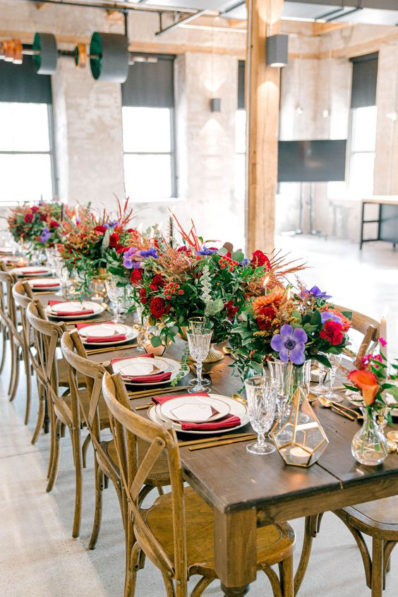 a colorful wedding tablescape with red napkins, red, pirple and orange blooms, greenery, feathers and fronds is a cool idea