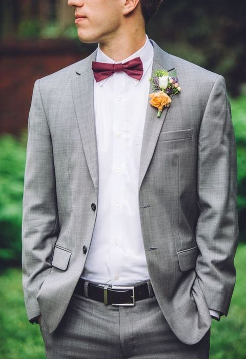 a grey suit, a burgundy bow tie and a pretty floral boutonniere for a stylish and modern groom's look
