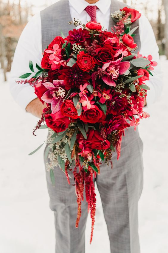 a grey waistcoat and pants, a red printed tie and a lush red and burgundy wedding bouquet with soem foliage