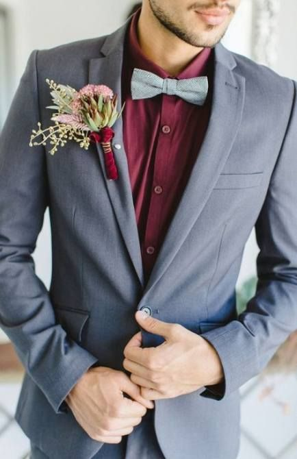 a grey wedding suit with a burgundy shirt and a grey bow tie plus a lush floral boutonniere for a modern groom