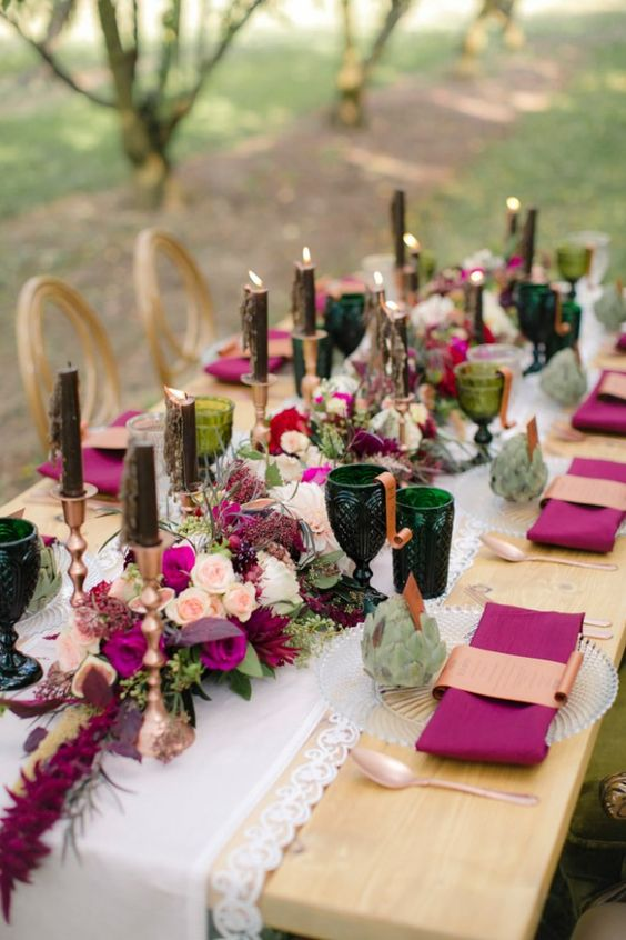 a jewel-tone wedding table setting with purple napkins and blooms, dark green candles and glasses, succulents