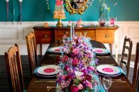 a jewel-tone wedding tablescape with a blue table runner, purple chargers and hot pink menus, blue napkins and pink, purple and fuchsia blooms