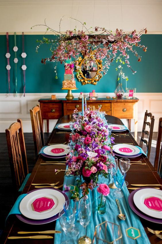 a jewel tone wedding tablescape with a blue table runner, purple chargers and hot pink menus, blue napkins and pink, purple and fuchsia blooms