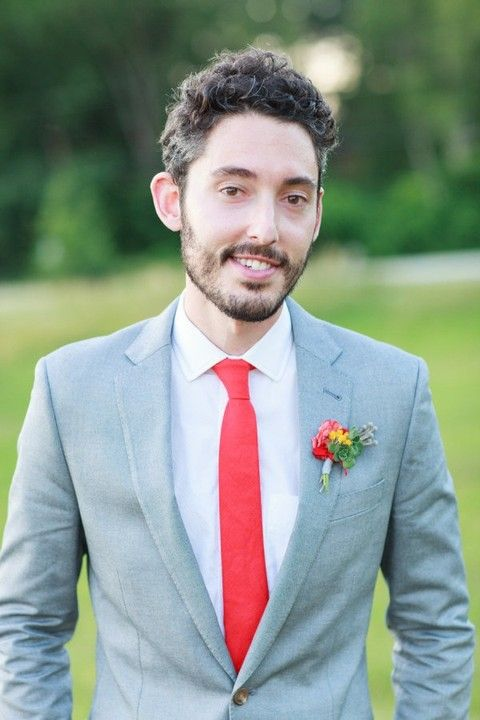a light grey suit, a red tie and a brigth boutonniere for a bold and chic groom's look