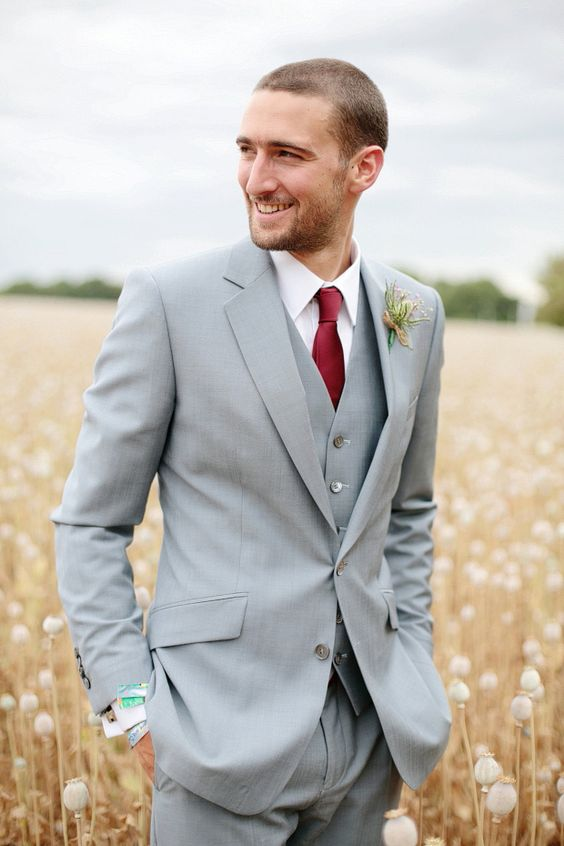 a light grey three-piece suit with a deep red tie is a stylish combo for a modern groom