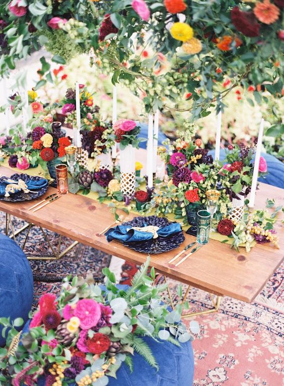 a lovely jewel tone wedding tablescape with red, burgundy, hot pink, fuchsia and yellow blooms and greenery, navy chargers and blue napkins