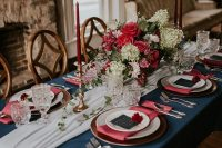 a lovely wedding tablescape with a navy tablecloth, pink napkins, pink and white blooms, navy menus and deep red candles