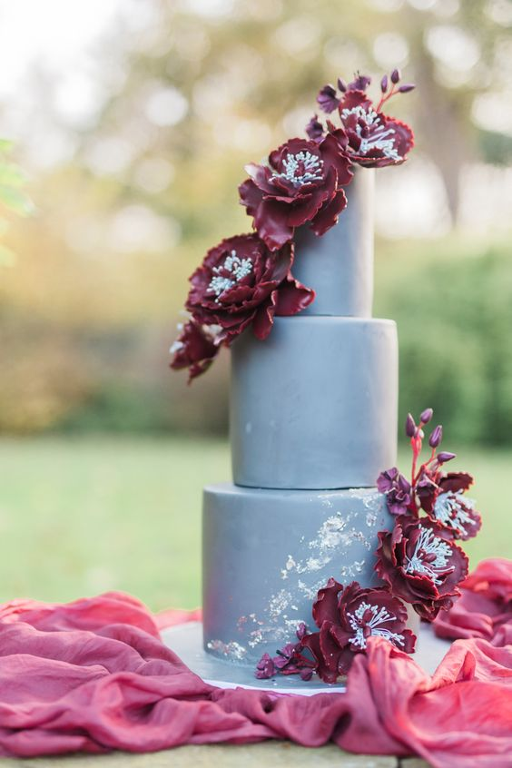a matte grey wedding cake with burgundy sugar flowers for a luxurious and refined wedding