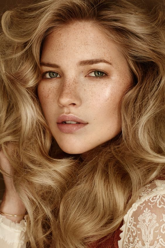 a nude glowy makeup with a shiny nude lip, highlighted eyebrows, highlighter and tone is very chic