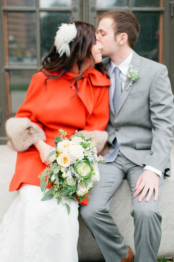 a red coat with a bow and faux fur sleeves to add a colorful accent and a grey suit for the groom