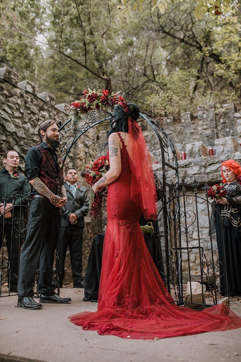 a red embellished mermaid wedding dress with a cutout back, a train and a matching veil