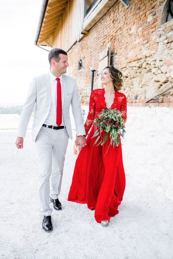 a red wedding gown with a lace bodice and sleeves and a plain skirt for this Christmas bride, the groom wearing a dove grey suit and a red tie