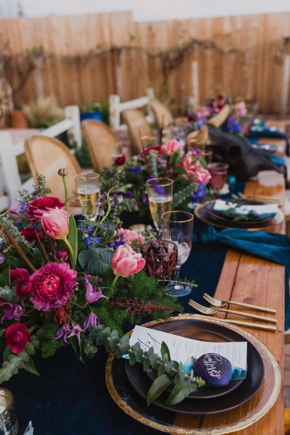 a refined jewel tone wedding tablescape with a navy table runner and napkins, pink, hot pink and purple blooms and greenery for the fall