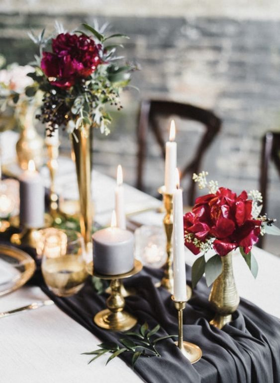a refined wedding tablescape with a graphite grey table runner, bold red and burgundy blooms, gilded candleholders and greenery