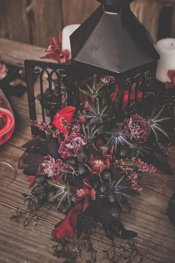 a sultry Tim Burton inspired wedding centerpiece of a lantern with black, purple and deerp red blooms and grapes