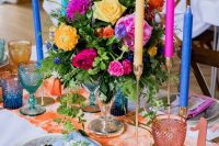 a sumptuous wedding tablescape with a peachy runner, glasses and a table number, navu, fuchsia candles, yellow and hot pink blooms