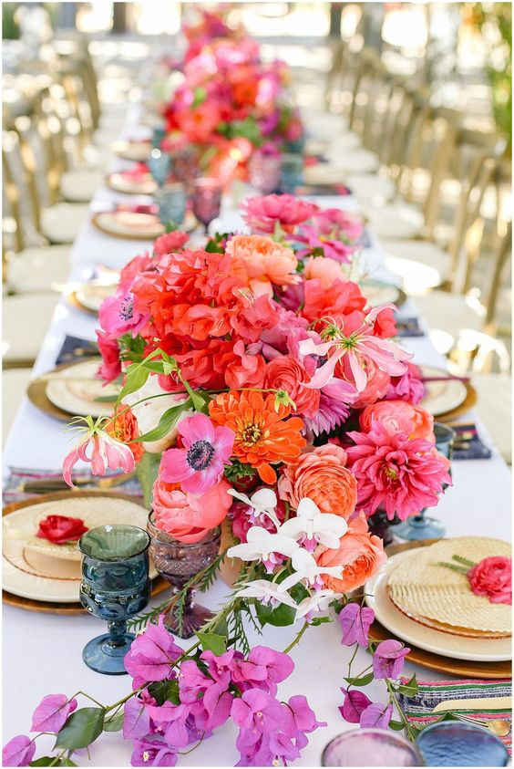a vibrant wedding table setting with orange, red, hot pink blooms, blue and purple glasses, gold chargers and cutlery is wow