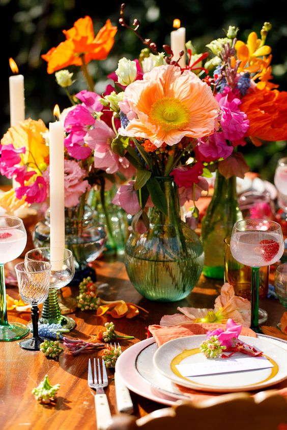 a vibrant wedding table setting with red, hot pink, orange blooms and greenery, candles, blush plates and glass candleholders