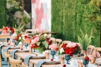 a vibrant wedding tablescape with blue napkins, a runner and glasses, pink and deep red blooms and gold candleholders