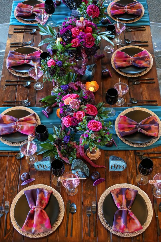 a vibrant wedding tablescape with blue runners, dip dye napkins, hot pink, fuchsia and purple blooms and blue agate stones