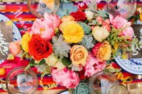 a vibrant wedding tablescape with red, pink, yellow blooms and succulents, a colorful table runner, plywood menus and yellow napkins