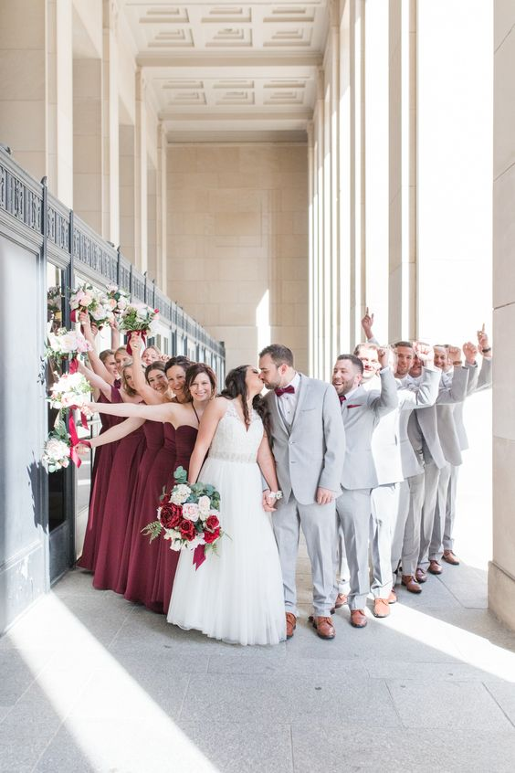 groomsmen wearing dove grey suits and burgundy accessories, bridesmaids wearing burgundy maxi dresses