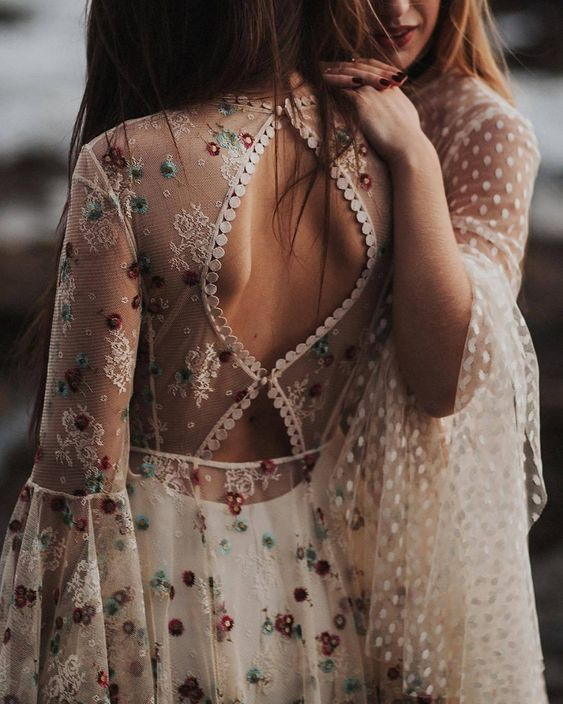 a boho wedding dress with a semi sheer bodice with lace appliques and colorful floral embroidery that add romance