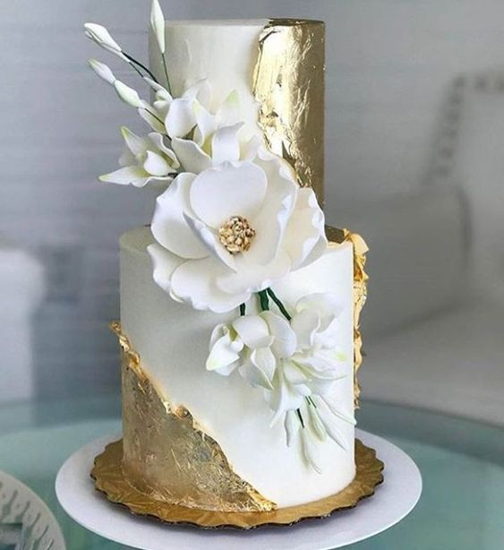 a breathtaking wedding cake in white with gold leaf, with sugar blooms is a real masterpiece