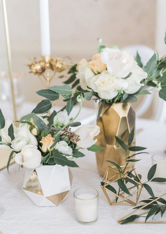 a chic modern wedding centerpiece of gold and white faceted vases, himmeli, white blooms and greenery