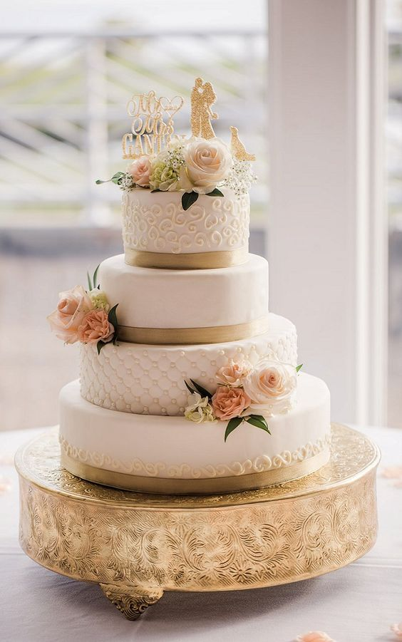 a chic wedding cake in white, with patterns and textures, gold ribbons and blush and pink blooms and greenery