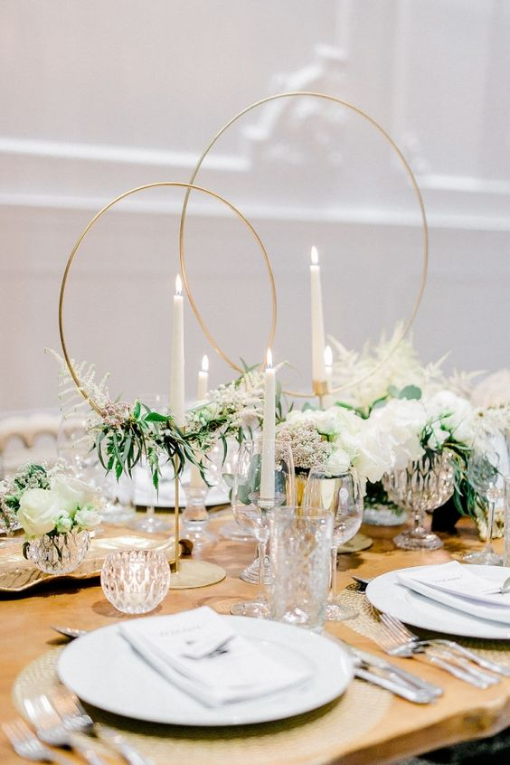 a chic wedding tablescape with white florals and greenery, with gold circles and woven placemats and crystal candleholders