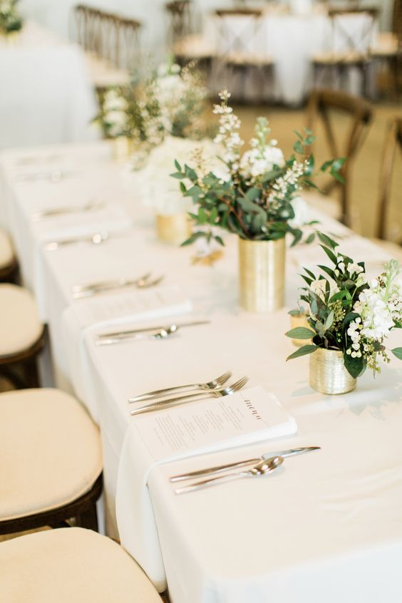 a classic white and gold wedding tablescape with gold vases, white blooms and greenery and chic cutlery